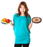 A pregnant smiling woman is holding food Stock Images