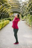 Pregnant sporty woman with neck pain after exercising. Pregnant fitness woman suffering from neck pain after training outdoor on early autumn park. Pregnancy royalty free stock photography
