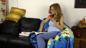 Pregnant student girl read book on sofa and eat apple fruit stock footage