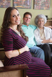 Pregnant Surrogate Woman with Parents. Grinning pregnant surrogate female sitting with happy parents Royalty Free Stock Photography