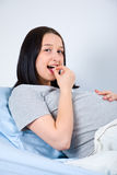 Pregnant taking vitamin pill Stock Image