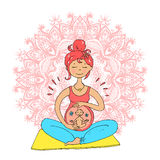 Pregnant tanned woman in lotus position against mandala backgrou Stock Photos