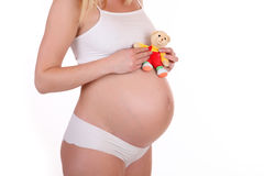 Pregnant Teen with soft toy bear. Pregnant Teen is standing there with a stuffed animal in front of white isolated background. Close up photo of the big baby royalty free stock photography
