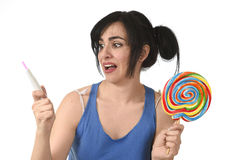 Pregnant teenager holding big lollipop while checking positive pink result on pregnancy test Stock Photos