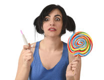 Pregnant teenager holding big lollipop while checking positive pink result on pregnancy test Royalty Free Stock Photo