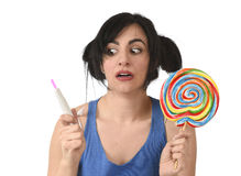Pregnant teenager holding big lollipop while checking positive pink result on pregnancy test Stock Photo