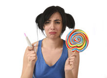 Pregnant teenager holding big lollipop while checking positive pink result on pregnancy test Royalty Free Stock Images