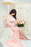 Pregnant in  tender peach dress sits on chair Royalty Free Stock Photo