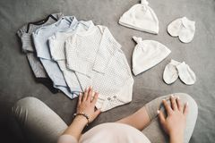 Pregnant unrecognizable woman sitting with baby clothes. Top view stock photos