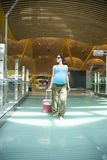 Pregnant walking at airport hall Royalty Free Stock Images