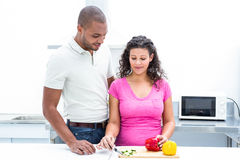 Pregnant wife chopping vegetable while husband looking at her Royalty Free Stock Photos