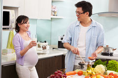 Pregnant wife drinking milk watching her husband Royalty Free Stock Photos