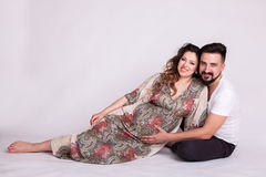 Pregnant wife with her husband in studio photo. Wife and husband. Parenthood and expecting baby royalty free stock photography