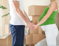 Pregnant wife holding hands of her husband in new home. Cute pregnant wife holding hands of her husband standing front of boxes during moving in new home stock image