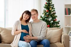 Pregnant wife with husband at home at christmas Stock Photo