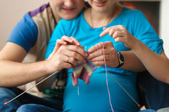 Pregnant wife and husband knitting stock images