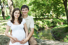 Pregnant wife and husband outdoors Stock Photo