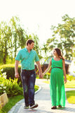 Pregnant wife and husband walking in park Stock Images