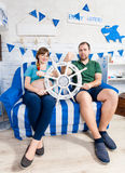 Pregnant wife and man posing with yacht helm at living room Stock Image