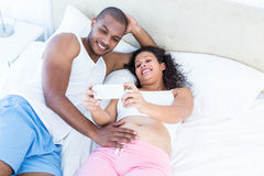 Pregnant wife showing smartphone to husband Royalty Free Stock Photography