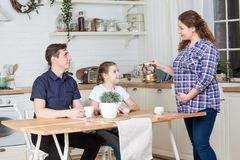Pregnant wife with teapot preparing breakfast to husband and teen age daughter at a kitchen. Pregnant wife with teapot preparing breakfast to husband and teen stock photography