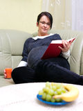 Pregnant woman. At home, reading and drinking juice Royalty Free Stock Photography