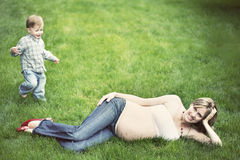 Pregnant woman. Attractive pretty pregnant blonde woman showing her belly laying in grass in park wearing jeans and red shoes, toddler boy son running towards stock photos