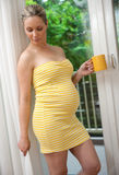 Pregnant woman. Relaxing next to window with coffee Stock Photo