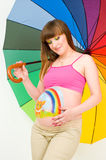 A pregnant woman. With body painting under an umbrella Stock Photo