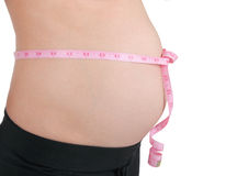 Pregnant woman. With pink tape measure on her belly. Isolated on white background Royalty Free Stock Photography