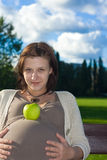 Pregnant woman. With apple on belly Royalty Free Stock Image