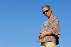 Pregnant woman - 7th month. Blond caucasian pregnant woman against blue sky Stock Photo