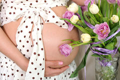 Pregnant woman abdomen with flowers. Royalty Free Stock Photography
