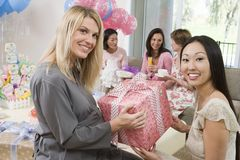 Pregnant Woman Accepting Gift At A Baby Shower. Portrait of friend giving gift to pregnant women at a baby shower stock image