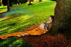 Pregnant woman against tree. Full body portrait of a pregnant woman wrapped in silk against a large tree Royalty Free Stock Image