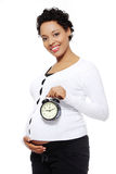 Pregnant woman with an alarm clock. Royalty Free Stock Image