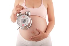 Pregnant woman with alarm clock Royalty Free Stock Photo