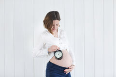 Pregnant woman with a alarm clock Stock Photography