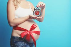 Pregnant woman with an alarm clock. A pregnant woman with an alarm clock posing against a blue background royalty free stock photography