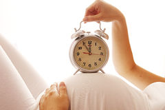 Pregnant woman with an alarm clock on a white background Royalty Free Stock Images