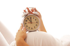 Pregnant woman with an alarm clock on a white background Stock Photography