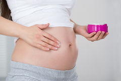 Pregnant Woman Applying Cream On Her Belly Royalty Free Stock Photos