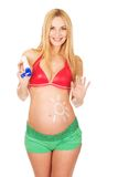 Pregnant woman applying sun cream on her belly Royalty Free Stock Photography