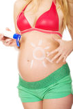 Pregnant woman applying sun cream on her belly Stock Images