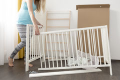Pregnant woman assembling bed for expectant baby. Young pregnant woman assembling bed for expectant baby Stock Images