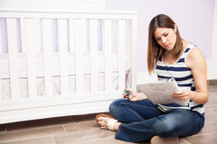 Pregnant woman assembling a crib Stock Images