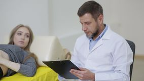 A doctor examines a pregnant woman and records the testimony in a medical record stock footage