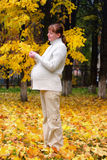Pregnant woman in autumn park hold maple leaf #1. Pregnant woman in autumn park hold maple leaf Royalty Free Stock Images