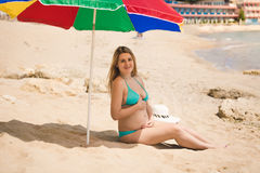 Pregnant woman awaiting baby relaxing on beach under parasol Stock Image