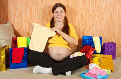 Pregnant woman with  babies clothes Stock Photos